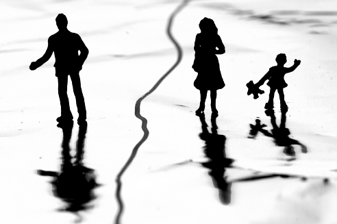 Silhouette of a family of three with a line separating the man from the wife and child.